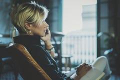 Stående av att le affärskvinnan som talar med partnern på smartphoneapparaten, medan arbeta avlägset i affärslopp fotografering för bildbyråer