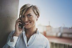 Stående av att le affärskvinnan som talar med partnern på smartphoneapparaten, medan arbeta avlägset i affärslopp arkivbilder