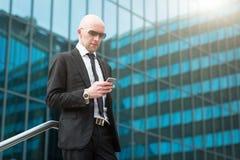 Stående av att le affärsmannen genom att använda den smarta telefonen för mobil royaltyfri fotografi
