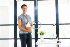 Stående av att le anseende för afro--amerikan kontorsarbetare i offfice Royaltyfri Fotografi