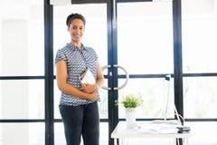 Stående av att le anseende för afro--amerikan kontorsarbetare i offfice Arkivbild