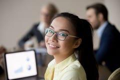 Stående av att le asiatisk anställd som ser kameran under möte arkivfoton