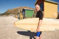 Stående av att le bärande surfingbrädaanseende för man mot strandkoja Arkivfoton