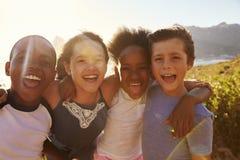 Stående av att le barn som står på klippor vid havet royaltyfri fotografi