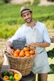 Stående av att le bondeanseende vid nya apelsiner i behållare royaltyfria foton