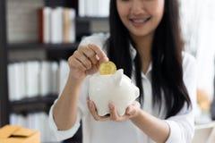 Stående av att le den asiatiska det hållspargrisen och myntet för ung kvinna royaltyfria bilder