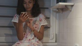 Stående av att le den bärande pajamaen för ung afro- amerikansk kvinna och att skriva på hennes mobiltelefon stock video