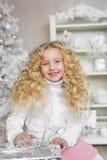 Stående av att le den blonda lilla flickan på en soffa med en gåvaask i jul Arkivfoto