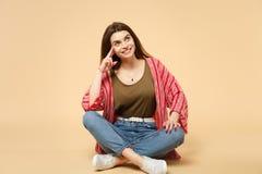 Stående av att le den eftertänksamma gulliga unga kvinnan i tillfällig kläder som sitter som ser upp isolerad på den pastellfärga arkivbilder