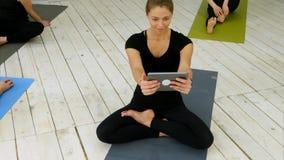 Stående av att le den färdiga kvinnan som använder den digitala minnestavlan som har video pratstund, medan sitta på yoga som är  Arkivfoto
