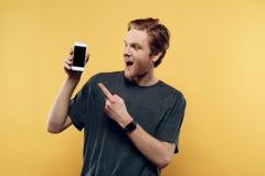 Stående av att le den hållande smartphonen för man royaltyfri foto