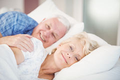 Stående av att le den höga kvinnan som kopplar av förutom man på säng Arkivfoto