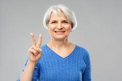 Stående av att le den höga kvinnan som visar fred arkivbilder