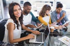 Stående av att le den idérika affärsmannen genom att använda bärbara datorn på kontorsskrivbordet royaltyfria bilder