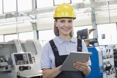Stående av att le den kvinnliga arbetaren som använder den digitala minnestavlan i fabriks- bransch arkivbild