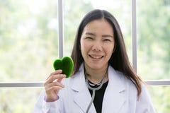 Stående av att le den kvinnliga doktorn med grön hjärta Vänskapsmatch dig arkivfoton