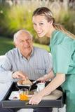 Stående av att le den kvinnliga sjuksköterskan Serving Breakfast arkivfoton