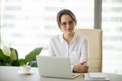 Stående av att le den lyckade affärskvinnan som poserar på kontoret de fotografering för bildbyråer