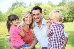 Stående av att le den lyckliga familjen utomhus Arkivbild