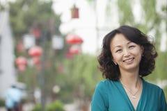 Stående av att le den mitt- vuxna kvinnan i Nanluoguxiang, Peking, Kina Royaltyfri Fotografi