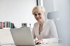 Stående av att le den mogna affärskvinnan som i regeringsställning använder bärbara datorn på skrivbordet arkivbilder