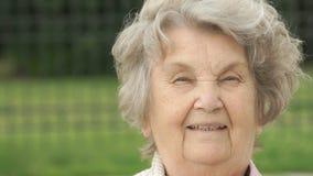 Stående av att le den mogna gamla kvinnan utomhus arkivfilmer