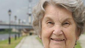 Stående av att le den mogna gamla kvinnan utomhus lager videofilmer