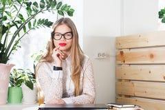 Stående av att le den nätta unga affärskvinnan i exponeringsglas som sitter på arbetsplats Royaltyfria Foton