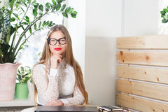 Stående av att le den nätta unga affärskvinnan i exponeringsglas som sitter på arbetsplats Royaltyfri Foto
