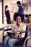 Stående av att le den rörelsehindrade affärsledaren i rullstol genom att använda den digitala minnestavlan royaltyfria foton