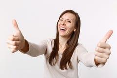 Stående av att le den skratta attraktiva unga kvinnan i ljus kläder som visar tummar som isoleras upp på vit väggbakgrund royaltyfri foto
