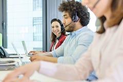 Stående av att le den unga affärskvinnan som använder hörlurar med mikrofon och bärbara datorn med kollegor i förgrund på kontore Royaltyfri Foto