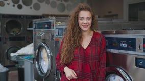 Stående av att le den unga härliga kvinnan med rött lockigt hår i röd tartanskjorta Loundry Infdoor långsam rörelse stock video