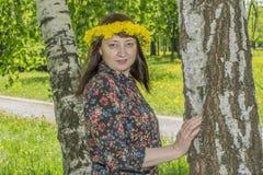 Stående av att le den unga kvinnan i blommakrans på gräsplanen fotografering för bildbyråer