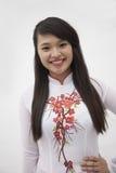 Stående av att le den unga kvinnan med långt hår som bär en traditionell klänning från Vietnam, studioskott Royaltyfria Foton