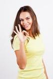 Stående av att le den unga kvinnan som okay göra en gest Royaltyfri Bild