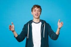 Stående av att le den unga mannen i tillfällig kläder som gör en gest visa format med horisontalworkspace som isoleras på blått royaltyfri foto