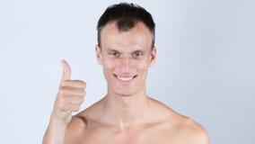 Stående av att le den unga topless mannen med tummen upp Royaltyfria Foton