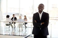 Stående av att le det svarta affärsmananseendet som i regeringsställning poserar royaltyfri foto