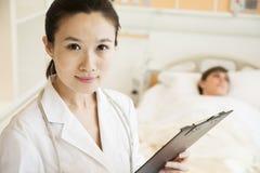 Stående av att le doktorn som rymmer ett medicinskt diagram med tålmodign som ligger i en sjukhussäng i bakgrunden Arkivbild