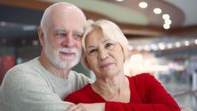 Stående av att le förälskade höga par Lyckligt familjanseende och krama på galleriablicken på kameran arkivfilmer