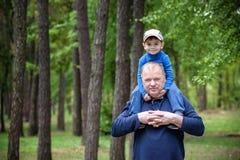 Stående av att le fadern som på ryggen ger hans ritt för son utomhus mot våren eller sommar Forest Park royaltyfria foton