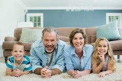 Stående av att le familjen som tillsammans ligger på matta i vardagsrum Royaltyfri Fotografi
