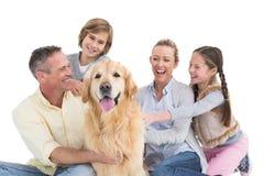 Stående av att le familjsammanträde samman med deras hund Arkivbilder