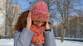 Stående av att le flickan i varmt lag och färgrik stucken hatt och halsduk som har rolig det fria under solig dag i vår stock video