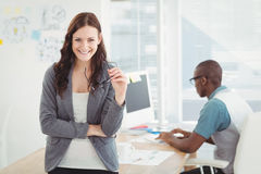 Stående av att le hållande glasögon för affärskvinna med coworkeren som arbetar på datorskrivbordet royaltyfria bilder