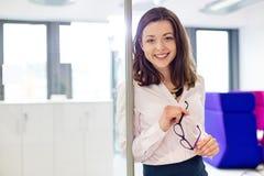 Stående av att le hållande glasögon för ung affärskvinna i regeringsställning arkivbild