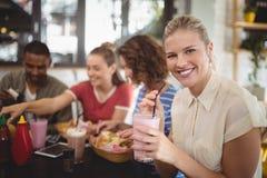 Stående av att le hållande milkshake för ung kvinna på kafét Arkivfoto