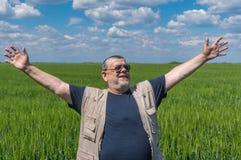 Stående av att le högt bondeanseende inom omoget skördfält arkivfoto