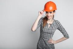 Stående av att le hjälmen för byggmästare för affärskvinna som den bärande isoleras på vit arkivfoto
